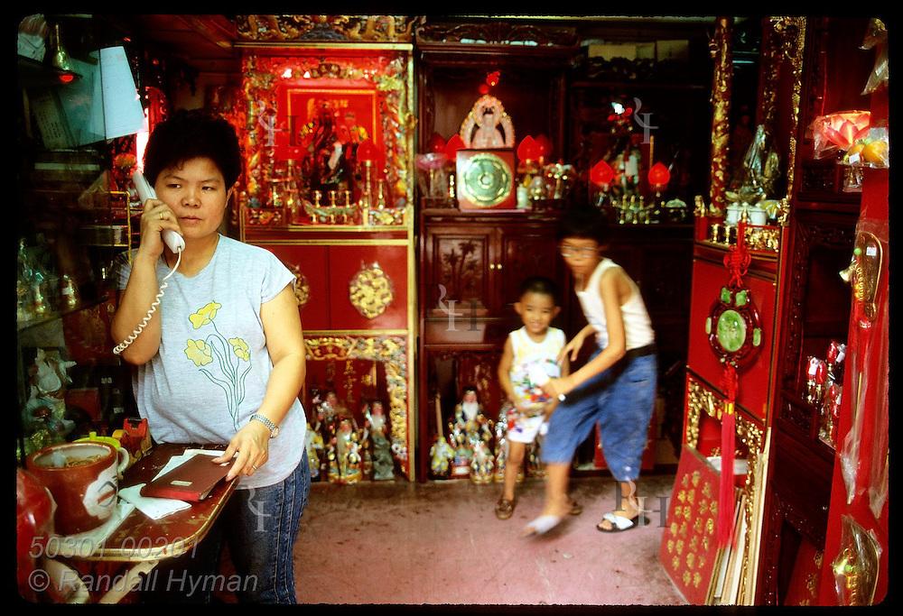 Woman talks on phone in her Feng Shui store as kids run around behind her; Yau Ma Tei, Kowloon. Hong Kong