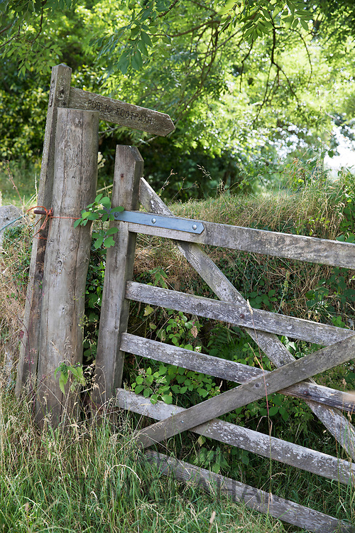 Walking trail signposted by Public Footpath sign in a rural scene on Dartmoor in Devon, UK
