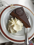 The famous chocolate Sacher Torte with whipped cream photographed at the Sacher Hotel in Vienna where the desert originated