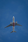A Boeing 777-F1H jet airliner A6-EFF with Emirates flies overhead in blue skies on its flight-path into London Heathrow airport, on 8th August 2018, in London, England.