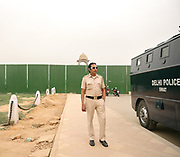 A policeman watches the crowd at the Gate of India.