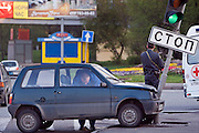 Moscow, Russia 13/05/2007..A policeman watches as a member of an ambulance crew inspects the inside of a drunken driver's car after he crashed into a stop sign at at a road junction. The man was uninjured but was so drunk he could not walk without assistance.