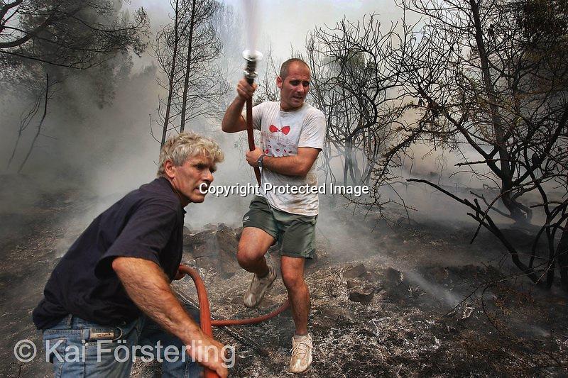 V. 12. Valencia, 13/08/2004. Dos voluntarios ayudan a sofocar el incendio que arrasa desde anoche la Sierra Calderona en el que se han quemado unas setecientas hectáreas y han sido desalojadas alrededor de 6.000 personas desde anoche. EFE / Kai Försterling.