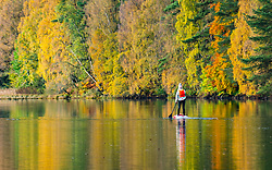 Pitlochry, Scotland, UK. 24th October 2021. A paddle boarder on Loch Faskally enjoys the tranquility of their surroundings as the bright autumn colours of the surrounding forest are reflected in the water.  Iain Masterton/Alamy Live News.