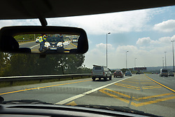 140418 Johannesburg. Winnie Madikizela-Mandela funeral. In the rearview mirror, National Traffic Police wait at the Malibongwe onramp to the N1 in order to close it off to traffic when the motorcade came past later in the day. Picture: Karen Sandison/African News Agency (ANA)