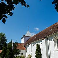 Ormslev Kirke ved Aarhus i solskin. Folkekirken i blå himmel, kirkegård