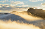Morning fog rises from the Russian River on Christmas morning, 2015, and pours over  the gap between Red HIll and  Peaked Hill in Sonoma Coast State Park, Jenner, California.