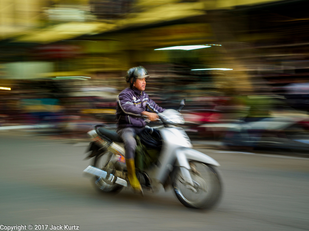 "21 DECEMBER 2017 - HANOI, VIETNAM:  Motorcycle traffic in the old quarter of Hanoi. The old quarter is the heart of Hanoi, with narrow streets and lots of small shops but it's being ""gentrified"" because of tourism and some of the shops are being turned into hotels and cafes for tourists and wealthy Vietnamese.  PHOTO BY JACK KURTZ"