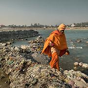A sadhu goes through Garbage along the Ganges. In Rishikesh.