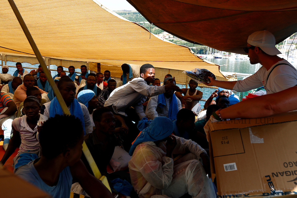 A Medecins san Frontiere (MSF) official distributes sandals to Sub-Saharan migrants sitting on the deck of the Migrant Offshore Aid Station (MOAS) ship MV Phoenix in Vibo Valentia, Italy, July 31, 2015.  195 migrants who were rescued off Libya on Wednesday arrived in Italy on Friday afternoon. The Phoenix, manned by personnel from international non-governmental organisations MSF and MOAS, is the first privately funded vessel to operate in the Mediterranean.<br /> REUTERS/Darrin Zammit Lupi <br /> MALTA OUT. NO COMMERCIAL OR EDITORIAL SALES IN MALTA