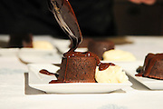 Chocolate souffle with vanilla ice cream and chocolate sauce the sauce being applied