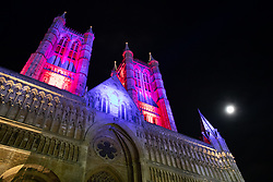 """© Licensed to London News Pictures. 08/12/2019. Lincoln, UK. The new Lincoln Cathedral floodlights could be seen at the annual Christmas Market for the first time this year. The market which attracts thousands of visitors every year was one of the first events to experience the new lighting which has been installed over the past year. The coloured lights change colours from red into blue during a moving sequence. Dr Anne Irving, programme manager of Lincoln Cathedral Connected, said that the commissioning of the new lighting system is a major milestone in the ongoing project.<br /> She said: """"We're delighted to be another step closer to the completion of the Old Deanery Visitor Centre next year.<br /> """"Lighting the cathedral is a very visual expression of the excitement we feel as the project nears completion.""""<br /> She added that the new lights will not only be much more environmentally friendly, but also provide better illumination of the historic building. The Reverend Canon John Patrick, Subdean of Lincoln, said that lighting the cathedral sent out a powerful message of hope.<br /> He said: """"The imagery of light is a powerful metaphor in the Christian story; light overcoming darkness, good defeating evil and hope triumphing over despair.<br /> """"The lighting of the cathedral not only is a daily reminder of the beauty of the building but also an important image of God's presence in this city and county."""". Photo credit: Dave Warren/LNP"""
