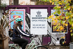 © Licensed to London News Pictures. 28/11/2020. Manchester, UK. A cyclist passes an anti-Tory sign in Norther Quarter, Manchester. Manchester will enter Tier 3. Photo credit: Kerry Elsworth/LNP