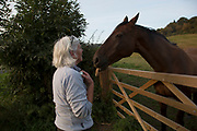Woman checks on on her horses in Kilburn on the edge of the North York Moors. Yorkshire, England, UK. This is a farming area where rural living and the countryside is at the centre of life in this county.