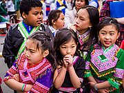 """29 APRIL 2017 - MINNEAPOLIS, MINNESOTA: Children from Thailand watch entertainers at the Songkran Uptown celebration. Several thousand people attended Songkran Uptown on Hennepin Ave in Minneapolis for the city's first celebration of Songkran, the traditional Thai New Year. Events included a Thai parade, a performance of the Ramakien (the Thai version of the Indian Ramayana), a """"Ladyboy"""" (drag queen) show, and Thai street food.     PHOTO BY JACK KURTZ"""