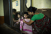 Before being dressed up, Rachi, 7, a disabled girl affected by microcephaly and myoclonic epilepsy, is being dried with a towel by her mother Jyoti Jadav, 34, a '1984 Gas Survivor', while inside their home near Saifiya College, in Bhopal, Madhya Pradesh, central India.