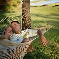 Couple relaxing in hammock, Waimea Plantation Cottages, Waimea, Kauai, Hawaii .