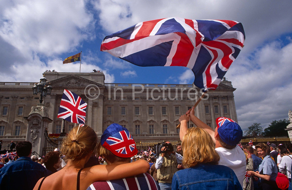 Londoners wave flags outside Buckingham Palace during 1995 VE Day 50th anniversary celebrations in London. The crowd of royalists have gathered outside the palace gates to sing their national anthem and wave their union jack flags. In the week near the anniversary date of May 8, 1945, when the World War II Allies formally accepted the unconditional surrender of the armed forces of Germany and peace was announced to tumultuous crowds across European cities, the British still go out of their way to honour those sacrificed and the realisation that peace was once again achieved. Street parties now – as they did in 1945 – played a large part in the country's patriotic well-being.