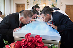 © Licensed to London News Pictures. 21/04/2018. Cobham, UK. Paddy Doherty (R) and his brothers kiss the casket at funeral of their mother Queenie, Elizabeth Doherty from Sacred Heart Church in Cobham, Surrey. Elizabeth Doherty, whose son Paddy Doherty is known for appearing on My Big Fat Gypsy Wedding and winning Celebrity Big Brother 8, died of a heart attack earlier this month. Paddy Doherty claimed his mother has died of a 'broken heart' following the death of her husband almost a year ago. Photo credit: Peter Macdiarmid/LNP