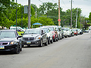 21 MAY 2020 - DES MOINES, IOWA: People in cars line up at an emergency food distribution in Evelyn K. Davis Park in central Des Moines. All of the 485 meals were distributed in about an hour. The economic fallout of the pandemic is being felt throughout Iowa. On May 21, 2020, Iowa reported that 187,375 people had filed for unemployment since the beginning of the COVID-19 pandemic and resulting economic shutdown. Emergency food pantry use has also increased in that time, as many Iowans in low wage jobs used emergency food banks and pantries for the first time. The Food Bank of Iowa said Thursday that demand in April 2020 was 31% higher than demand in April 2019, mostly because of unemployment caused by the Coronavirus (SARS-CoV-2) pandemic. The emergency food distribution Thursday was organized by the city of Des Moines, Food Bank of Iowa, Central Iowa Shelter and Services, Urban Dreams and Orchestrate Hospitality.     PHOTO BY JACK KURTZ