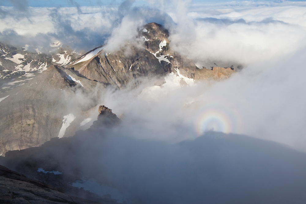 Hikers on the summit of Longs Peak project Brocken spectre and glories on clouds overtaking Chiefs Head, Rocky Mountain National Park, Colorado.