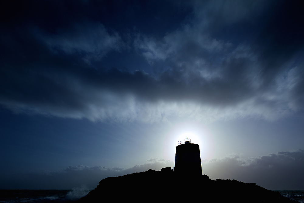 Noirmont Point Tower silhouetted against dark moody clouds in the sky in Jersey, Channel Islands