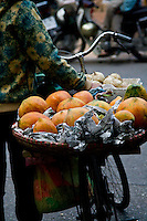 A basket of paw paw sitting on the back of a vendors bicycle.