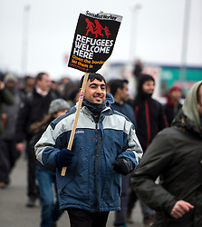 © Licensed to London News Pictures. 23/01/2016. Calais, France. A man holding a Socialist Worker sign as a group of migrants storm towards the port of Calais in Northern France during a demonstration through the town centre of Calais, on the same day that Leader of the Labour Party JEREMY CORBYN visited the migrant camp known as the 'Jungle' . Photo credit: Ben Cawthra/LNP