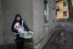 MSF nurse Ksinia Tsvierkornova waits outside the apartment block as she prepares to enter the home of Nina and Ivan Prokopenko in Debaltsevo.