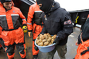 Deckhand Benjamin Potts delivers a bucket full of hardened organic waste balls - to be used for throwing practice by the crew members.  Four crew members who threw the farthest and most accurately in a contest were given throwing positions, where they held responsiblity for throwing bottles of butyric acid (rotten butter) during confrontations with the Japanese whaling fleet.