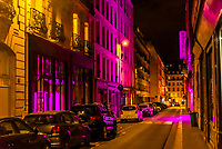 Magenta neon light illuminates the street at night, Rue Amelie, Paris, France.
