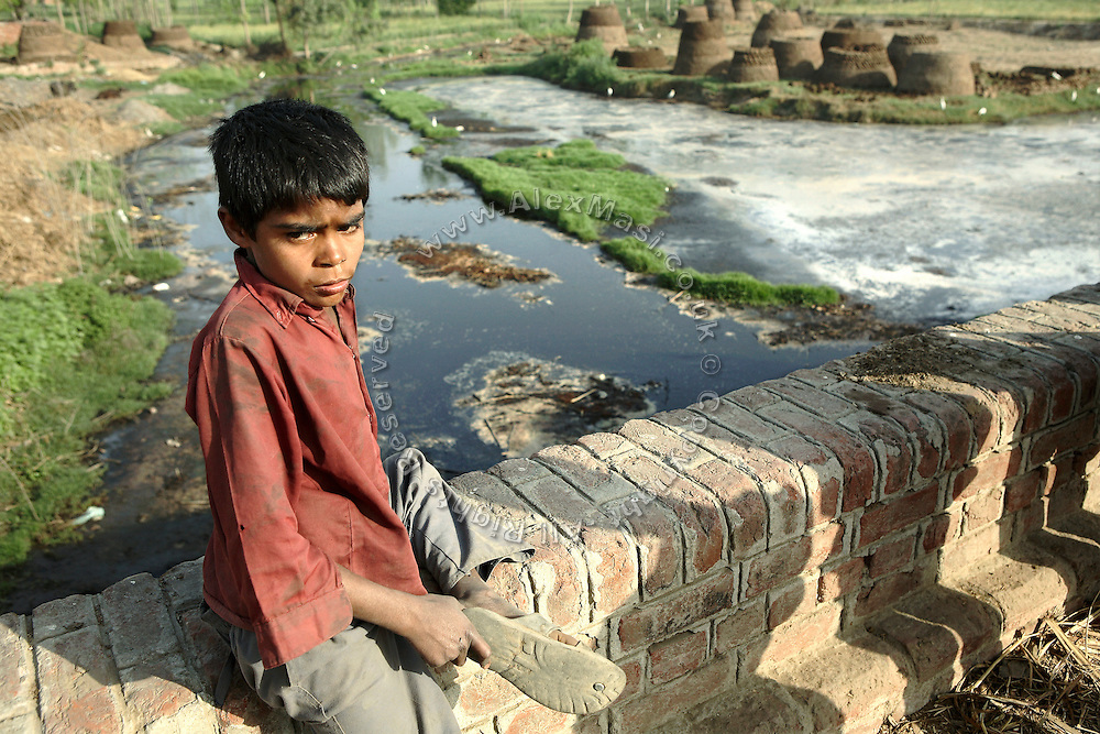 A young boy is portrayed while sitting on a bridge over the polluted waters of the Krishni river in the village of Bhanera Khemchand, pop. 2000, Saharanpur District, Uttar Pradesh, India, on Sunday, Apr. 6, 2008.