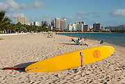 A rescue surf board sits waiting for an emergency at Ala Moana Beach Park with Waikiki and Diamond Head Crater in the background.