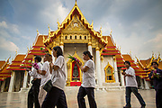"25 FEBRUARY 2013 - BANGKOK, THAILAND:  Thai Buddhists process around Wat Benchamabophit Dusitvanaram (popularly known as either Wat Bencha or the Marble Temple) on Makha Bucha Day. Makha Bucha is a Buddhist holiday celebrated in Myanmar (Burma), Thailand, Cambodia and Laos on the full moon day of the third lunar month (February 25 in 2013). The third lunar month is known in Thai is Makha. Bucha is a Thai word meaning ""to venerate"" or ""to honor"". Makha Bucha Day is for the veneration of Buddha and his teachings on the full moon day of the third lunar month. Makha Bucha Day marks the day that 1,250 Arahata spontaneously came to see the Buddha. The Buddha in turn laid down the principles his teachings. In Thailand, this teaching has been dubbed the 'Heart of Buddhism'.     PHOTO BY JACK KURTZ"