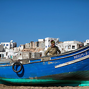 Un pêcheur vient de terminer le nettoyage de son embarcation. Il attend le tracteur qui doit venir le pacer sur les hauteurs de la plage.