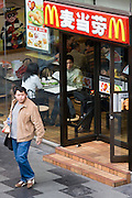 Chinese man leaves McDonalds fastfood restaurant on Nanjing Road, Shanghai, China