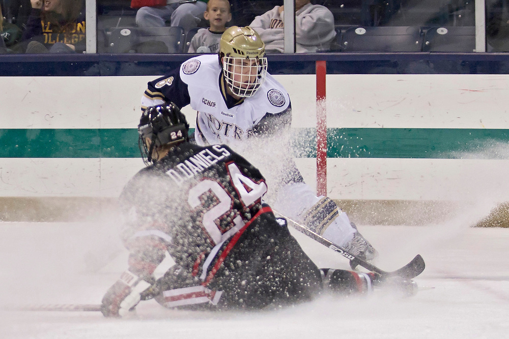 Notre Dame center Patrick Gaul (#6) and Northeastern forward Drew Daniels (#24) battle in second period action during NCAA hockey game between Notre Dame and Northeastern.  The Northeastern Huskies defeated the Notre Dame Fighting Irish 9-2 in game at the Compton Family Ice Arena in South Bend, Indiana.