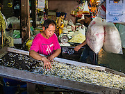 "12 JANUARY 2016 - BANGKOK, THAILAND: A vendor sorts bean sprouts in Khlong Toey Market in Bangkok. Khlong Toey (also called Khlong Toei) Market is one of the largest ""wet markets"" in Thailand. The market is located in the midst of one of Bangkok's largest slum areas and close to the city's original deep water port. Thousands of people live in the neighboring slum area. Thousands more shop in the sprawling market for fresh fruits and vegetables as well meat, fish and poultry.         PHOTO BY JACK KURTZ"