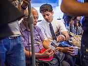 16 JULY 2013 - BANGKOK, THAILAND:   A missionary from the Church of Latter Day Saints, (LDS - Mormons) talks to a Thai Buddhist on the BTS Skytrain Sukhumvit line.     PHOTO BY JACK KURTZ