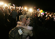 Janelle Hill, 22, of Marysville, WA, kisses her husband Cpl. Travis Hill as 260 members of 1st Battalion, 5th Marine Regiment, 1st Marine Division returned home Wednesday September 28, 2005 after deploying to Iraq for seven months in support of Operation Iraqi Freedom.