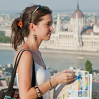 Tourist on summer sightseeing with the Hungarian Parliament in the background in Budapest, Hungary on August 25, 2011. ATTILA VOLGYI