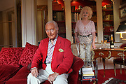 Wolf C Hartwig aged 91, producer of epic films and soft-porn features, with his fourth wife, and actress, Veronique Vendell in their apartment on Avenue de Foch, Paris. Wolf Hartwig was awarded a Bambi Award from German Cinema for his film 'The Iron Cross' which was directed by Sam Peckinpah starring James Coburn with Veronique Vendell. A producer working in exploitation genres, soft porn, sex, lurid, violent and sensational features. Other films he produced include 'Horrors from Spider Island'. 'Lady Hamilton' and 'Virgin of the Seven Seas'.//Wolf Hartwig and his wife Veronique Vendell in the salon. She serves champagne, he is sitting on the sofa