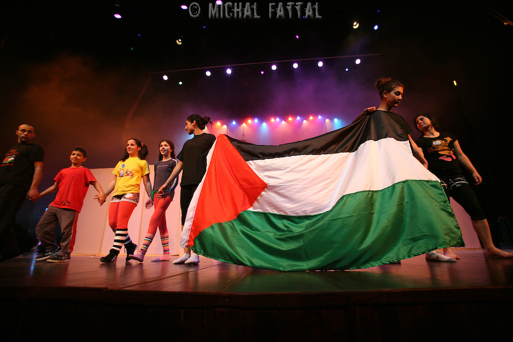 """The Palestinian Circus School members hold a Palestinian flag in the end of the show """"Circus behind the wall"""" in Ramallah, November 20, 2009. The circus group was established in 2006, in order to give a new way of expression for Palestinians, and a new way to deliver the idea of resistance to the occupation. This performance shows the life of Palestinians behind the separation wall. Photo by Michal Fattal/Backyard"""