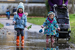 © Licensed to London News Pictures. 05/02/2021. London, UK. Gwendolyn Rixon age 4 (L) and Josephine Rixon age 2 (R) play in a large puddle of water in Chestnuts Park, north London. Part of the footpath in the park is flooded following heavy overnight rain in London. According to the Met Office, snow is forecast for the weekend. <br /> <br /> ***Permission Granted***<br /> <br />  Photo credit: Dinendra Haria/LNP
