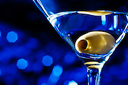 Blue Martini. Cool, refreshing, Martini with an olive on a sparkly blue background with bokah in a bar or nightclub.<br /> Beverage photgraphy.