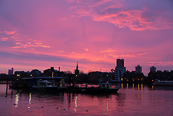 © Licensed to London News Pictures. 26/01/2014. London, UK. A colourful pink sunrise behind the Marine Police Unit pontoon reflects in the water on the River Thames in East London. Photo credit : Vickie Flores/LNP
