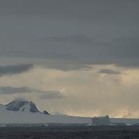 Mountains on the Antarctica Peninsula rise above the ocean near the Antarctic Circle.