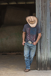 cowboy leaning against a barn with his head lowered