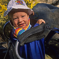 A youngster rides in a backpacking child carrier in California's Sierra Nevada
