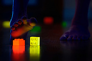 A bare foot stepping on glowing lego in a dark room.Black light